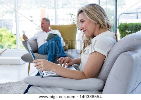Smiling woman with laptop and man using technology at home