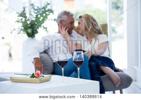 Romantic couple sitting on armchair with wine and gift box on foreground