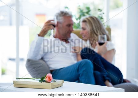 Rose and gift box on table with couple having red wine in background