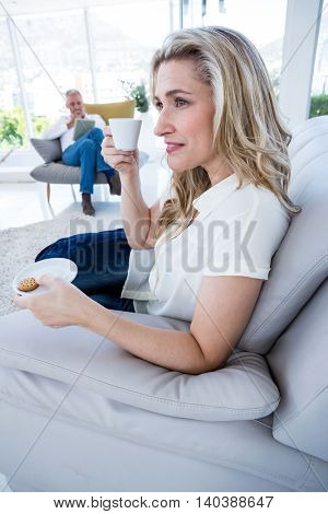 Smiling woman having coffee while sitting on sofa at home