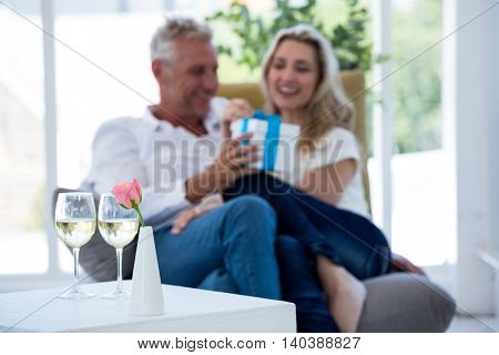 White wine on table with couple holding gift box in background
