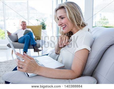 Cheerful woman with laptop and man using technology at home