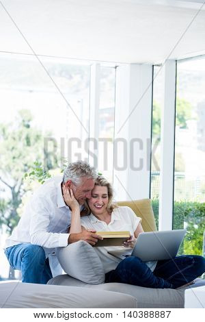 Romantic happy mature couple with gift box at home