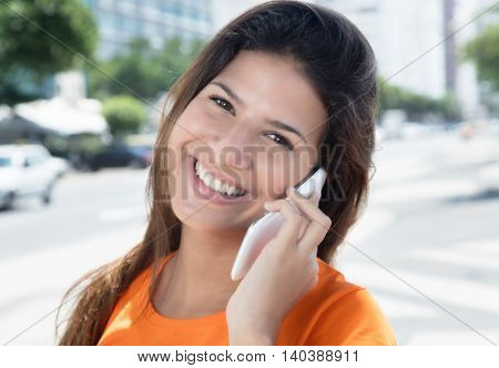 Laughing caucasian woman speaking at phone outdoor in the city in the summer