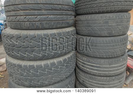 Old used car tires stacked on piles