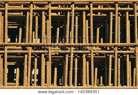 Rusty reinforcing mesh in heap on construction ground.
