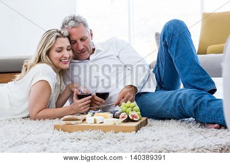 Cheerful couple with red wine and food while lying on rug at home