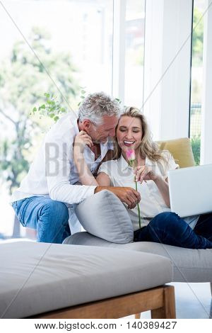 Romantic smiling mature couple with rose at home