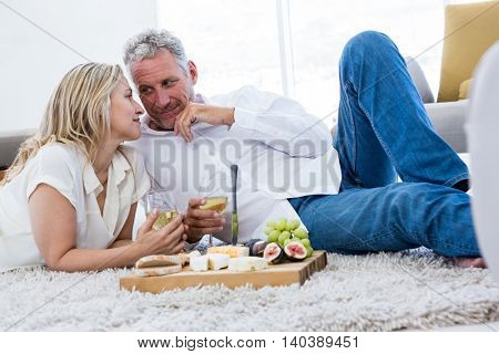 Romantic couple with white wine and food while lying on rug at home