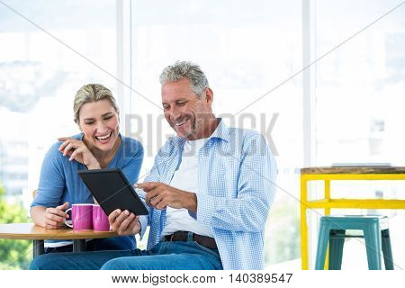 Smiling mature couple using digital tablet while sitting at restaurant