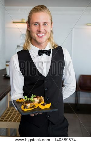 Portrait of waiter holding a plate of food in restaurant