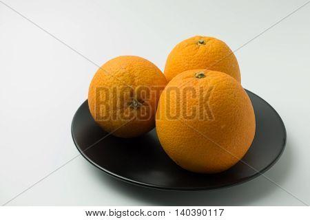 three orange on the plate on white background