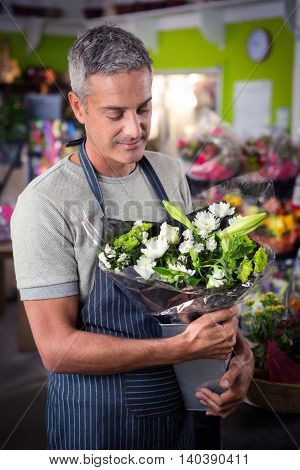 Happy male florist holding bunch of white flower in vase at his flower shop
