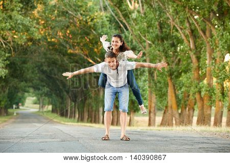 young couple walk on country road with high trees, romantic people concept, summer season