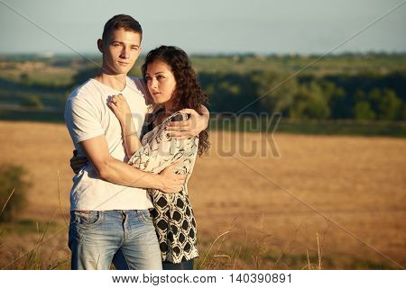 young couple posing on wheat field background, romantic and tenderness concept, summer season