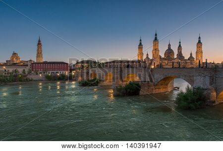 Basilica Our Lady Pillar In Zaragoza In Spain Shot From Another Bank Of The River In Sunset