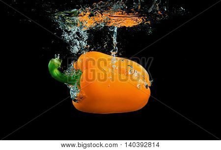 Bell pepper on black background with splashes