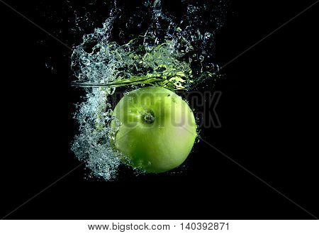 Green apple on black background with splashes