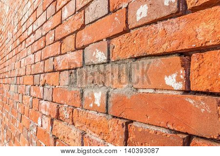 Close up texture of grungy red brick wall background.