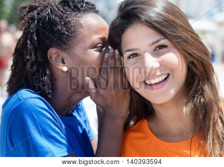 African american and caucasian girlfriend whispering outdoor in the city in the summer