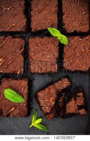 Homemade dark chocolate brownies decorated with strawberries and mint leaves over black slate background top view