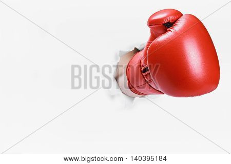 hand in boxing glove broke through the paper wall. Place an empty paper for your text