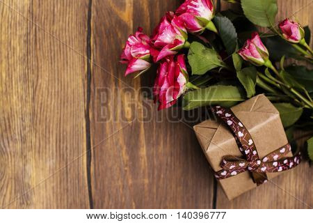 Mothers day or birthday greeting card with roses and gift box. Top view. Toned image