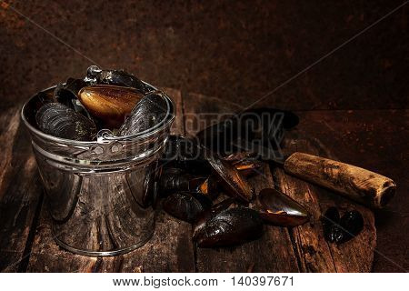 Cooked mussels in a bucket on a dark wooden background. gourmet Dinner