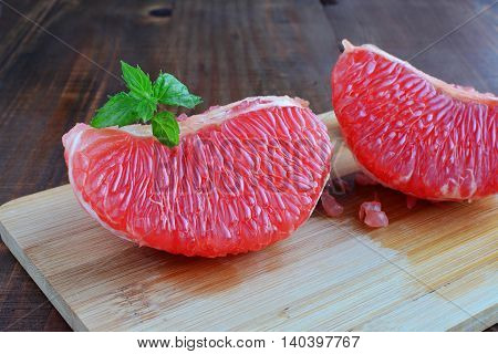 Pink grapefruit pieces with mint leaves on wooden board