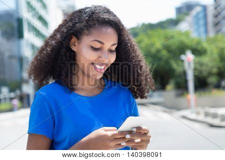 Happy latin woman surfing the net outdoor in the city in the summer