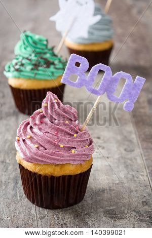 Sweet halloween cupcakes on rustic wooden background