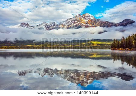 Picturesque Pyramid Mountain reflected in Pyramid Lake. Cold autumn morning in the Canadian Rockies. The concept of leisure and tourism
