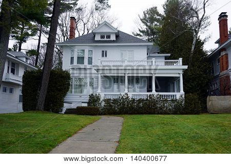 WEQUENTONSING, MICHIGAN / UNITED STATES - DECEMBER 22, 2015: A white home, with a wraparound front porch and balcony, on Beach Drive in Wequetonsing.