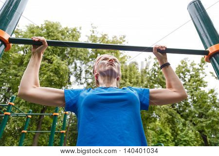 sport woman catch up with the horizontal bar outdoor