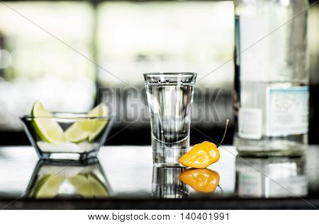 Tequila shot in a table bar with salt lemon and yellow habanero chilli pepper.