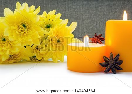 Yellow chrysanthemums with yellow two candles and two stars anise on the white background