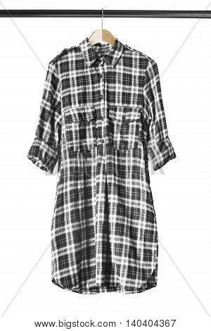 Black and white tartan shirt on clothes rack isolated over white