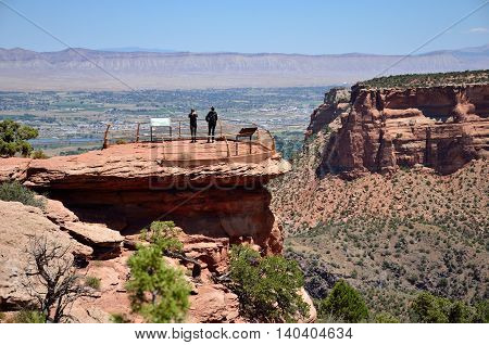 Two people stand on an observation area overlooking a canyon in the Colorado National Monument