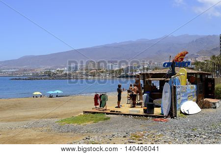 Playa De Las Americas beach Tenerife Canary Islands Spain Europe - June 18 2016: Surf shack with surfers and surf boards on the beach