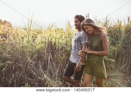 Romantic Young Couple Walking Together In Countryside