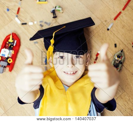 little cute preschooler boy among toys lego at home in graduate hat smiling posing emotional, lifestyle people concept, wooden floor