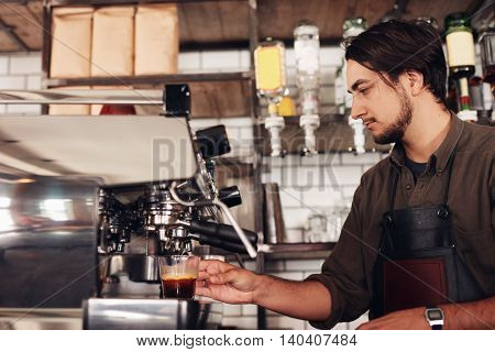 Side view of male barista preparing espresso at coffee shop. Young man in apron making coffee using coffee maker at the cafe.