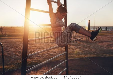 Woman Performing Hanging Leg Raises.
