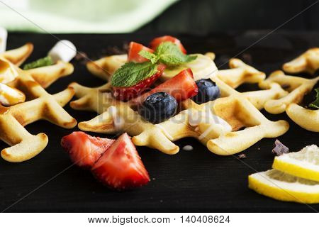Homemade thick belgium waffles over wooden background. Tasty breakfast concept. Toned image. Selective focus