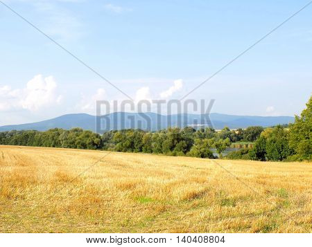 Field after harvest and hills in background