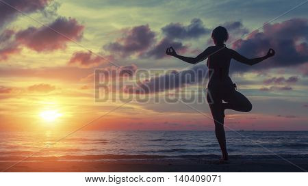 Yoga woman exercising on the beach during a stunning sunset. Peace, harmony, health and meditation.