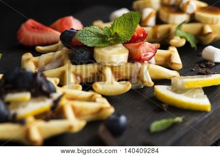 Thick belgium waffles with different toppings on wooden cutting board. Selective focus