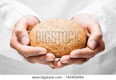 Human hands with bread closeup on white background