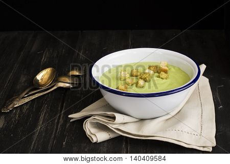 Green spinach and pea soup with croutons. Dark style. Selective focus. Space for text