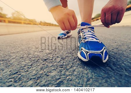 young woman runner tying shoelaces on sunrise bridge road